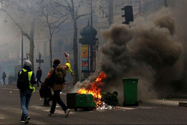 Une poubelle brûle à Paris le 8 décembre.