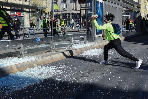 Un manifestant casse la vitre d'un arrêt du tramway, à Montpellier.