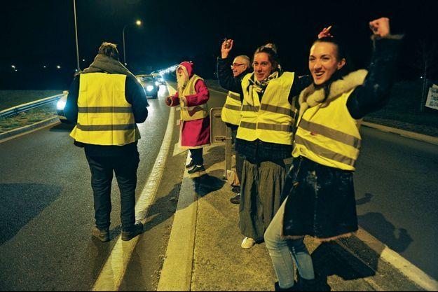 Vanessa (à g.), 31 ans, et Gwenaëlle, 29 ans, près de Villeblevin, dans l'Yonne, vendredi 30 novembre. Leur Père Noël distribue des bonbons aux automobilistes.