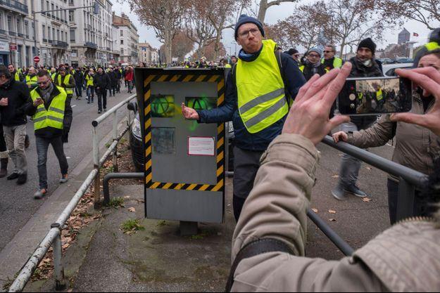 Un gilet jaune pose devant un radar dégradé à Lyon, samedi 5 janvier.
