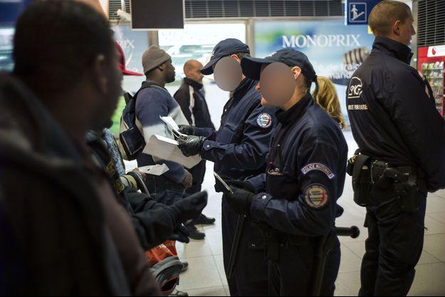 Des policiers contrôlent les documents de personnes, Gare du Nord, à Paris en 2012.