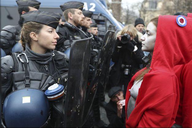 Une des Marianne de Deborah de Robertis devant une CRS sur les Champs-Elysées.