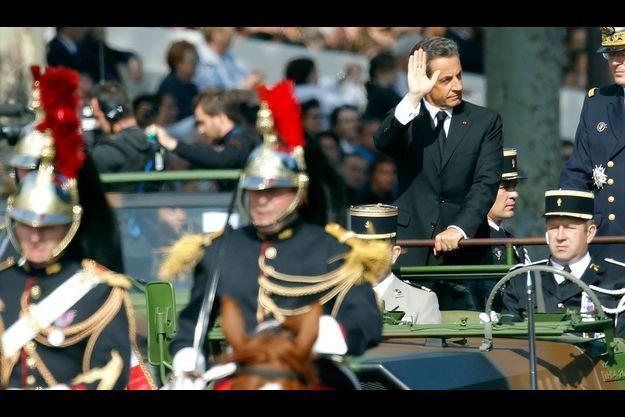Nicolas Sarkozy, jeudi matin, encadré par la garde républicaine sur les Champs-Elysées.