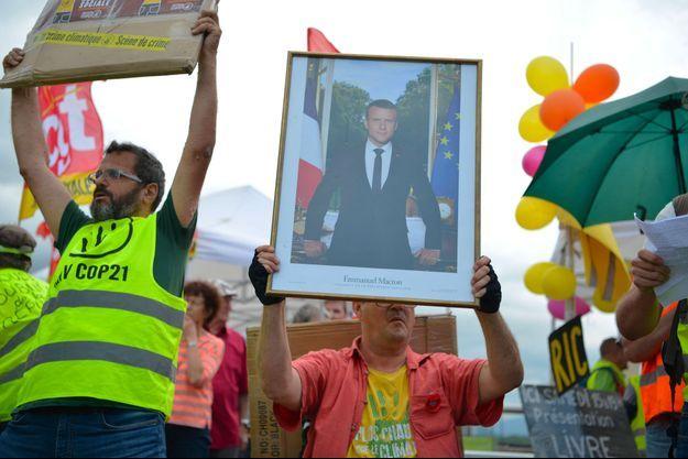 Des membres du collectif ANV-COP21, avec un portrait présidentiel, lors d'une manifestation contre la privatisation des barrages à Saint-Egrève dans l'Isère, le 15 juin.