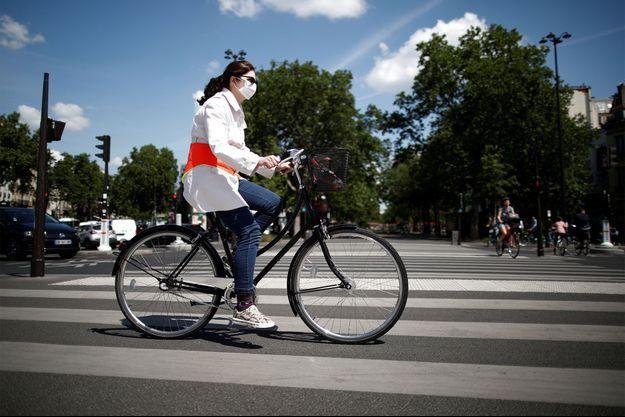 Une femme portant un masque fait du vélo à Paris après le déconfinement.