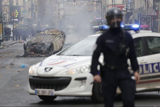 Un policier devant une voiture incendiée par des étudiants, le 3 décembre, à Aubervilliers.