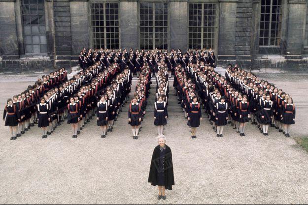 Un uniforme symbole du principe d'égalité : Février 1974, les lycéennes et leur intendante dans la cour de la maison d'éducation de Saint-Denis, située dans l'ancienne abbaye royale. Les classes de seconde portent la ceinture nacarat (rouge), celles de première, la blanche, la multicolore est réservée aux terminales. Des gants blancs et un béret complètent la tenue pour les cérémonies officielles.