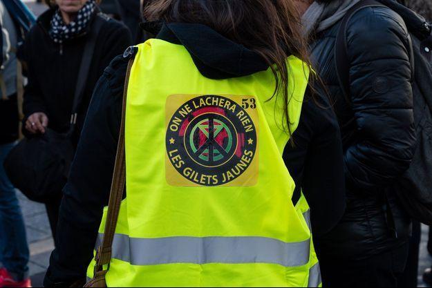"""Une jeune femme """"gilet jaune"""" ici à Paris fin février."""