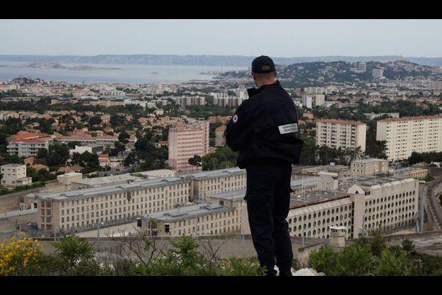 Vue plongeante sur le chaudron. Depuis une des calanques qui dominent la cité phocéenne, un surveillant de prison domine son terrain d'action, les bâtiments de la maison d'arrêt des Baumettes dans le IXe arrondissement de Marseille. Les femmes de prisonniers viennent sur cette hauteur pour parler avec leurs compagnons en contrebas. Au loin, à droite, la basilique Notre-Dame-de-la-Garde, la « bonne mère ».