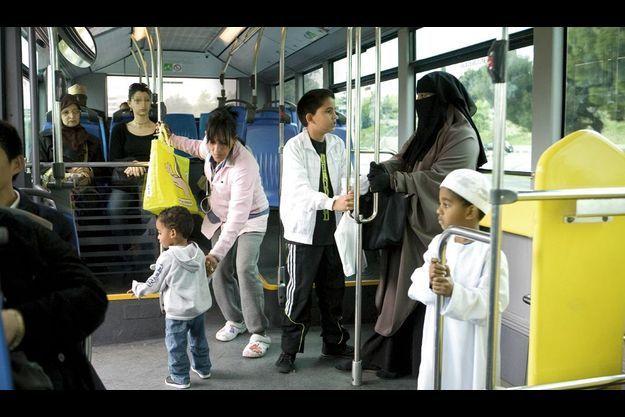 Vendredi 15 avril, dans un bus du XIIIe arrondissement de Marseille, en route pour le carnaval de l'école. Marie est avec sa mère, Nazek, 46 ans (en rose), son petit frère Abel, 9 ans (à sa droite), et ses deux enfants : Yanis, 4 ans, déguisé en émir, et Amine, 2 ans.