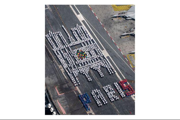 Les marins du porte-avions Charles de Gaulle formant la silhouette de la cathédrale Notre-Dame et le mot Paris.
