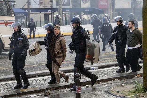 """Deux hommes arrêtés par des policiers à Paris, pendant l'acte 18 des """"gilets jaunes""""."""