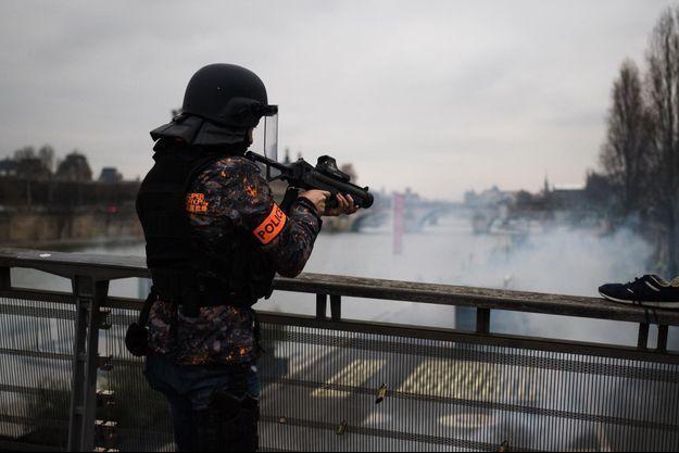 Un membre des forces de l'ordre utilisant les lanceurs de balles de défense (LBD).