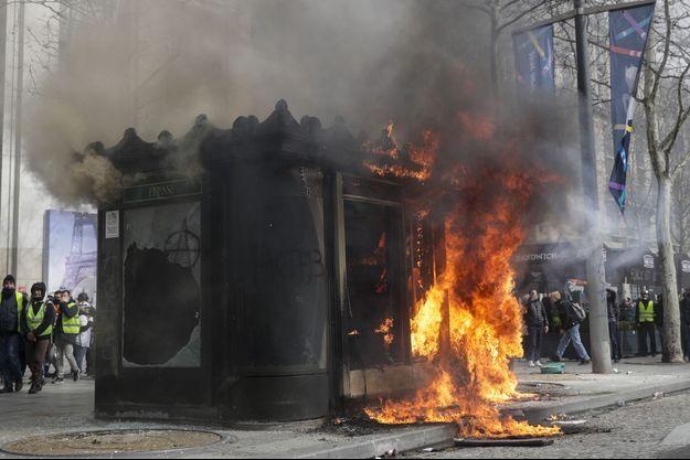 """Un kiosque en feu sur les Champs-Elysées lors de l'acte 18 des """"gilets jaunes""""."""