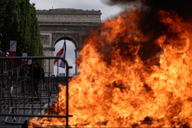 Tensions et poubelles incendiées sur les Champs-Elysées après le défilé du 14-Juillet.