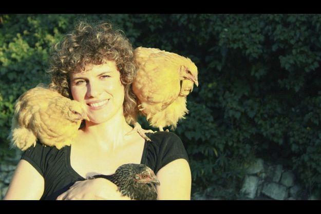 Elise Rousseau, auteur de « Tout pour ma poule » avec, dans les bras, Grosse Cotte, une marans, et, sur l'épaule, Plumette, une jeune orpington.