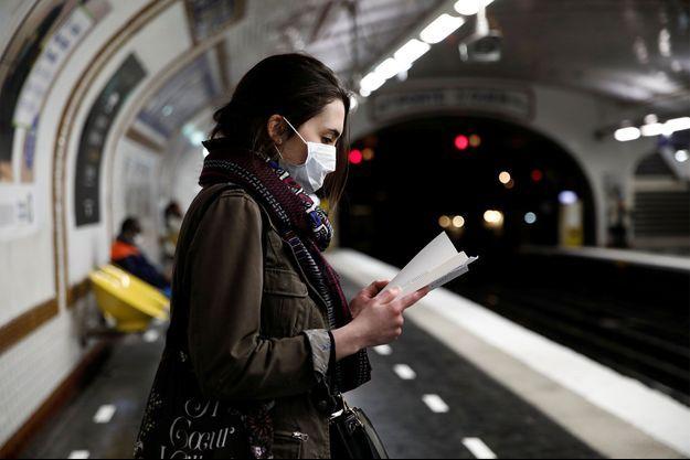 Une femme portant un masque dans le métro parisien.