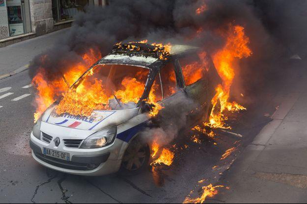 La voiture de police en flammes après avoir été attaquée par des casseurs.
