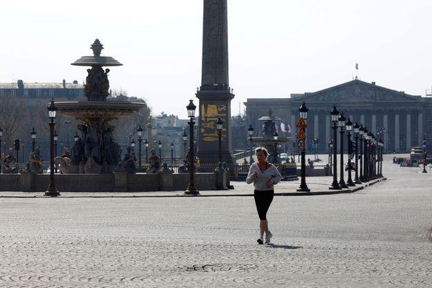 Place de la Concorde, une Parisienne fait son jogging dans la ville déserte.