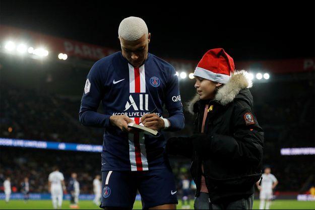 Kylian Mbappé, samedi, signe un autographe à un petit garçon venu sur le terrain.