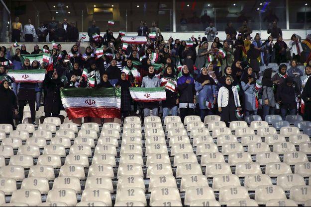 Des spectatrices iraniennes, présélectionnées par le gouvernement, chantent leur hymne national avant le début d'un match de football amical entre l'Iran et la Bolivie, au stade Azadi (Freedom), à Téhéran, en Iran, le mardi 16 octobre 2018.