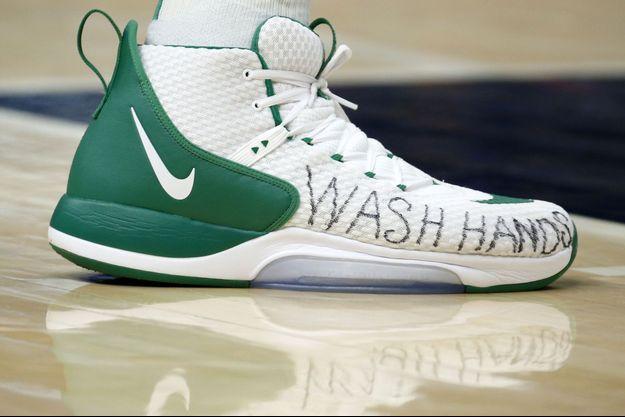 """Une chaussure d'un joueur de basket des Boston Celtics porte le message """"lavez-vous les mains""""."""