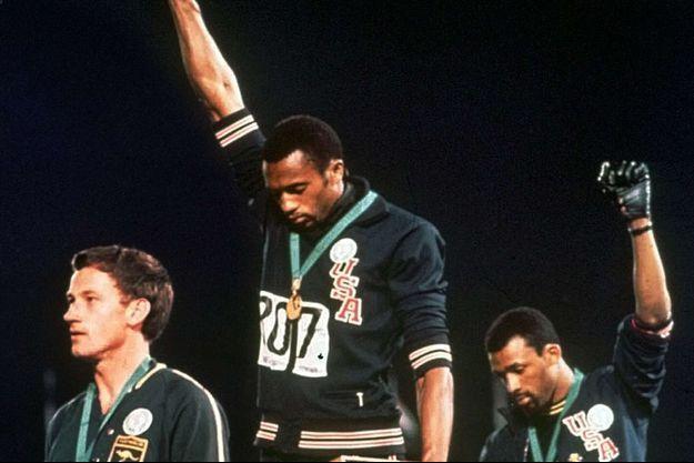 L'Australien Peter Norman, aux côtés des Américains Tommie Smith et John Carlos, tous les deux le poing levé lors des JO de Mexico, en 1968.
