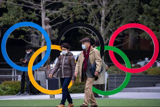 Des habitants marchent, masqués, devant le musée olympique de Tokyo.