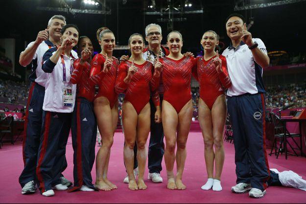 En 2012, l'équipe américaine de gymnastique aux Jeux Olympiques. Derrière elles, au milieu, leur entraîneur John Geddert.