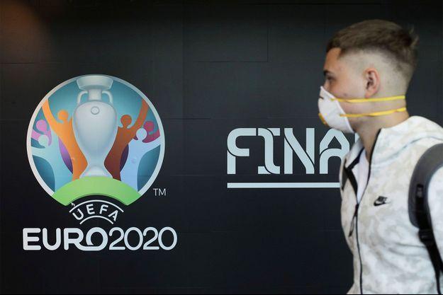 Un homme portant un masque à l'aéroport de Bucarest, ville qui devait accueillir l'Euro 2020.