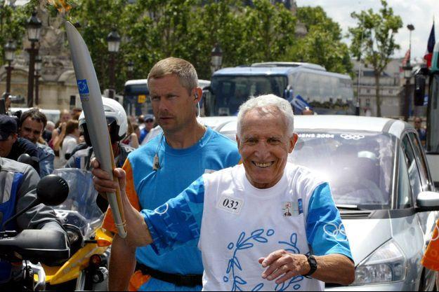 Alain Mimoun a porté la flamme olympique avant les Jeux Olympiques d'Athènes en 2004.