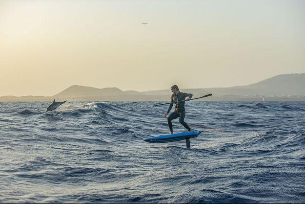 Ludovic Dulou, aux Canaries glisse sur son foil entouré de dauphins.