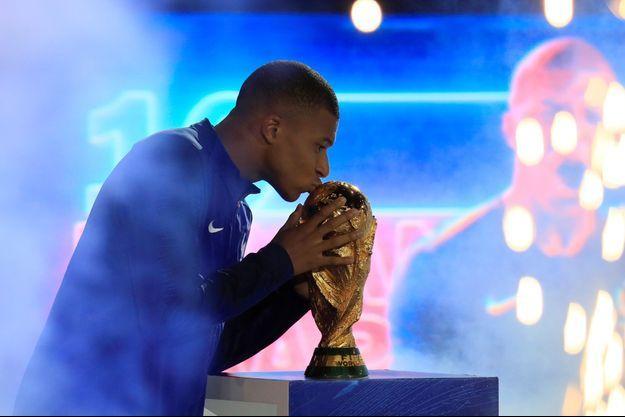 Kylian Mbappé embrasse le trophée de la Coupe du monde lors de la cérémonie organisée au Stade de France le 9 septembre.