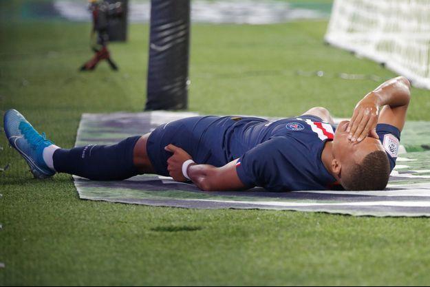 Kylian Mbappé, au sol, se tient la cuisse gauche.