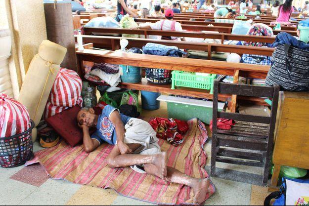 Un homme est allongé dans une église à Tacloban, aux Philippines.