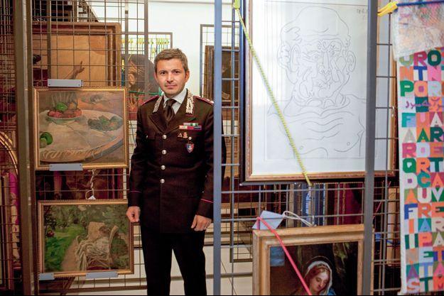 Le major Antonio Coppola dans les réserves du siège des carabiniers, à Rome. A sa droite, « La nature morte au petit chien », de Gauguin, et « La femme aux deux fauteuils » de Bonnard, volés en 1970 et retrouvés en avril dernier.