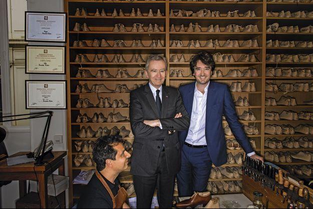 Bernard et Antoine Arnault dans l'atelier Berluti du 33 rue Marbeuf, devant la bibliothèque où sont alignées les formes en bois de chaque client. Avec Carlos, artisan de pied.