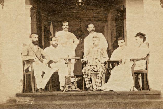 Premier homme à droite : Arthur Rimbaud, vers 1880, à Aden. A côté de lui, le patron de l'hôtel de l'Univers, Jules Suel (costume à carreaux).