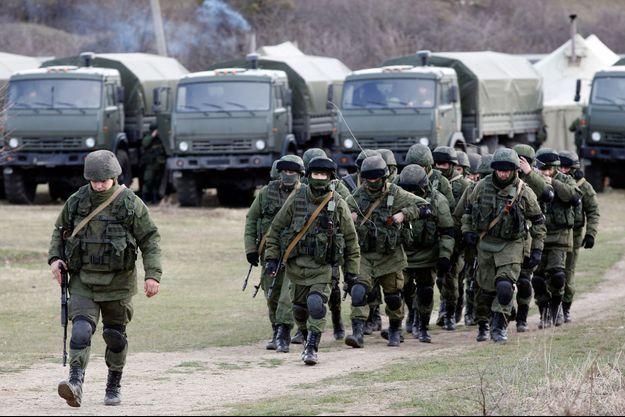 Des soldats probablement russes à proximité d'une base militaire ukrainienne à Perevalnoye, en Crimée, ce jeudi.