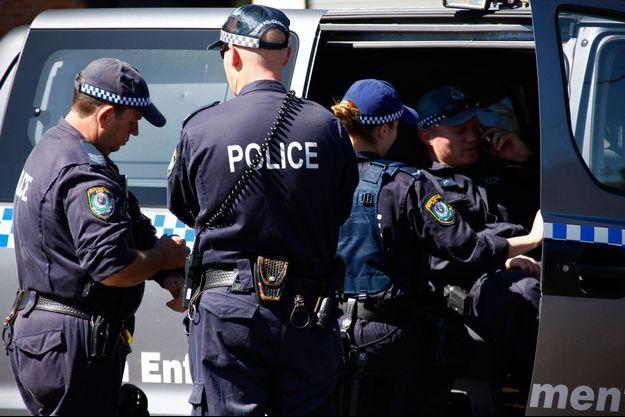 Jeudi, la police australienne discute dans les quartiers ouest de Sydney avant le début des opérations.