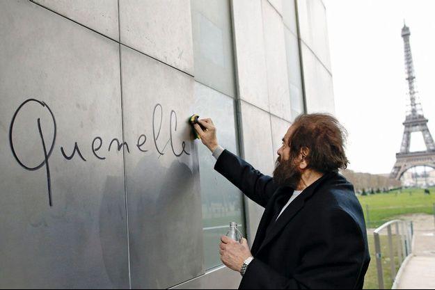 Le 6 janvier 2014, au Champ-de-Mars, à Paris. L'écrivain Marek Halter nettoie un grafti sur le Mur pour la paix.