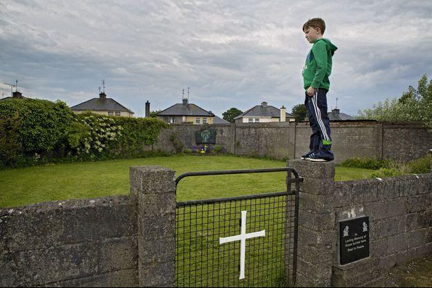 A Tuam, dans le lotissement de la Dublin Road, Matthew, 8 ans, près d'une plaque à la mémoire des victimes. Au fond, une petite statue de la vierge parmi les fleurs.