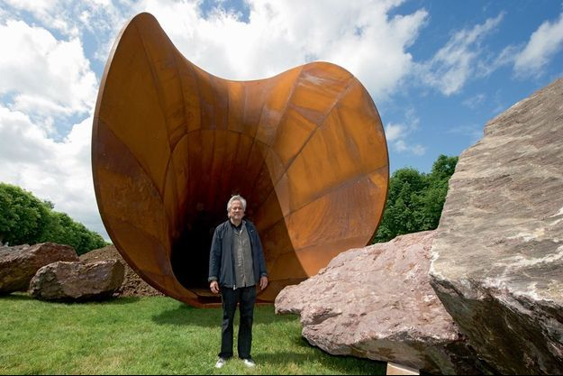 Derrière l'artiste, l'extrémité de l'œuvre centrale du « Dirty Corner » forme une vaste cavité de 10 mètres de haut en acier vieilli.
