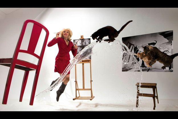 Amanda Lear prend la place de Salvador Dali pour une reconstitution de « Dali Atomicus », la célèbre photo du maître prise en 1948 par son ami le photographe Philippe Halsman.