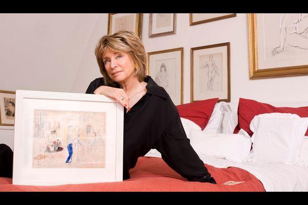 Danièle Thompson chez elle, avec le tableau qu'elle avait réalisé et cosigné, encore enfant, avec Raoul Dufy en 1953. Ce dessin ne fait pas partie de la vente aux enchères.
