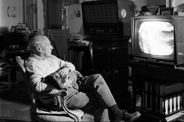 """Cannes, France, 11 octobre 1960. Le peintre espagnol Pablo Picasso regarde la télévision dans sa villa """"La Californie"""", avec son fidèle chien teckel """"Lump"""" sur les genoux."""