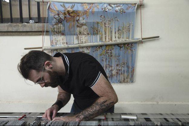 Johan, l'un des trois derniers canuts, penché sur un métier technologique unique au monde.