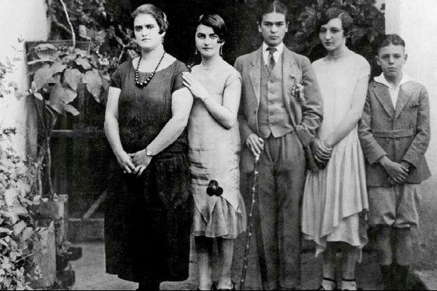 Dans le patio de la maison Bleue de Coyoacan, en 1926. Le garçon en costume trois-pièces qui pose pour son père avec sa mère, Matilde, et sa soeur Cristina (à gauche), c'est Frida.