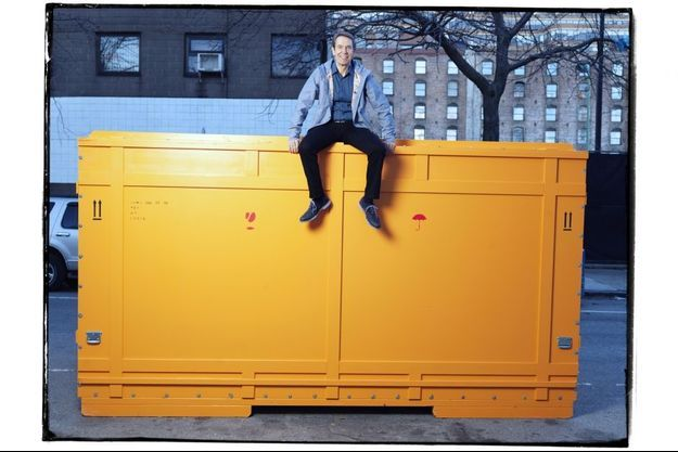 Jeff Koons assis sur une boîte de transport de l'une de ses oeuvres devant son atelier newyorkais.