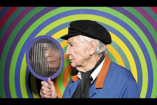Julio Le Parc pose devant « Surface couleur, série 23, n°14-11 » (1970-2012, acrylique sur toile, 200 cm x 200 cm) et tient dans la main son invention « Miroir » (1966, aluminium et Inox).